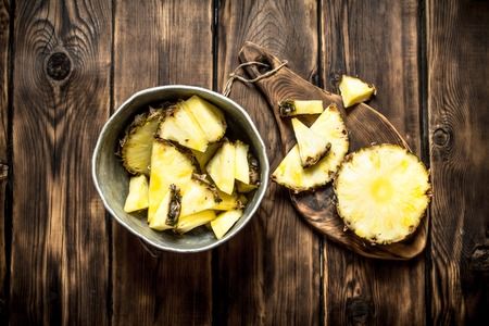 pan tropical: Slices of pineapple in a pot. On a wooden table.