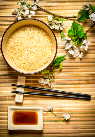 Japanese food. Bowl with rice, soy sauce and the cherry branches.