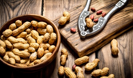 Peanuts in a bowl with a Nutcracker on the Board. On wooden background.