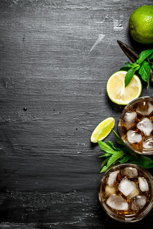 Rum with ice , mint and fresh lime. On a black wooden background.