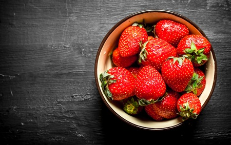 free dish: Ripe strawberries in a bowl. On the black wooden table.
