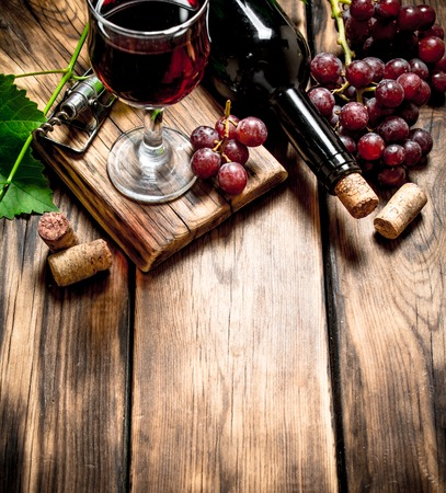 Red wine with a vine branch. On a wooden table. Stock Photo