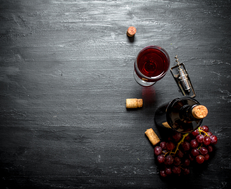 Bottle of red wine with a corkscrew. On a black wooden background. 版權商用圖片