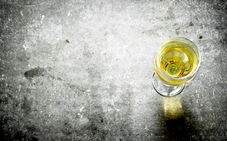 selective focus: glass of white wine. On the stone table.