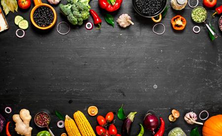 유기농 식품의 프레임입니다. 검은 콩 신선한 생 야채. 검은 칠판에.