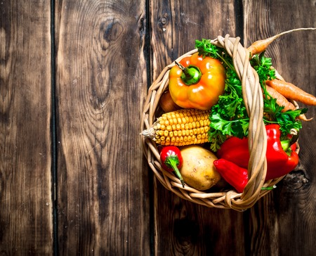 fruits in a basket: Organic food . Fresh vegetables in the old basket. On wooden background.