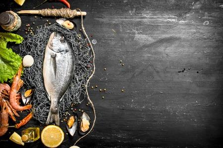 신선한 해산물. 새우, 레몬, 향신료와 신선한 생선입니다. 검은 칠판에.
