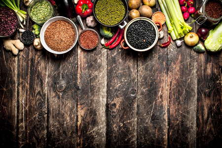 Organic Food. A variety of beans with fresh vegetables and spices. On the old wooden table. Stock Photo