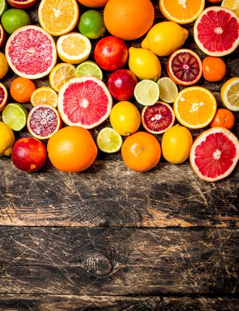 Fondo de cítricos. Frutas cítricas frescas: limones, naranjas, limas y pomelos. En el fondo de madera.