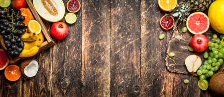 Various ripe fruits in a wooden box. On a wooden table.