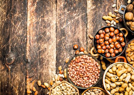 Various nuts in bowls. On wooden background.