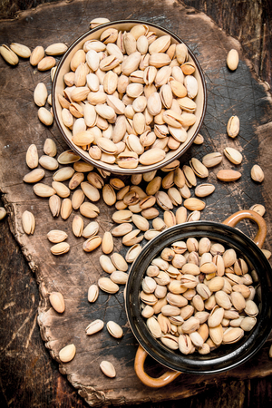 pistachios in a bowl on the Board. On wooden background.
