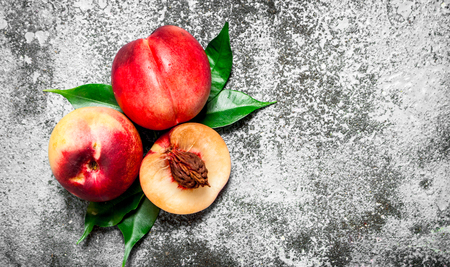 Fresh peaches with green leaves. On rustic background.