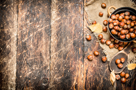 Hazelnuts in a bowl. On wooden background.
