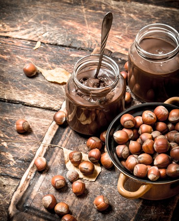 Nut butter with chocolate and hazelnuts. On wooden background.