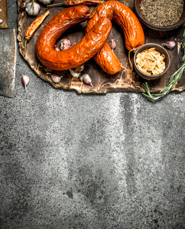 Krakow sausage with spices and garlic on the board. On a rustic background.