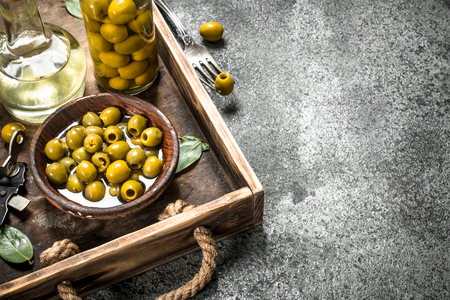 Olive oil with pickled olives on an old tray. On a rustic background.
