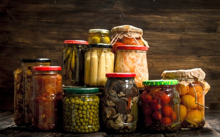 Preserves vegetables and mushrooms in glass jars. On a wooden background.