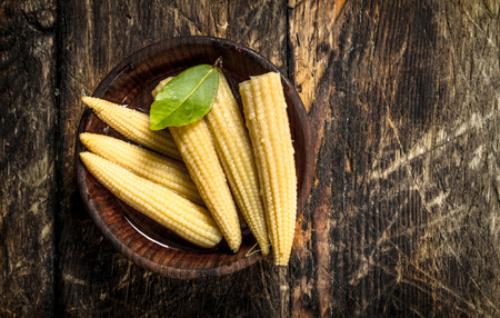 Pickled corn in a bowl. On a wooden background. Stock fotó