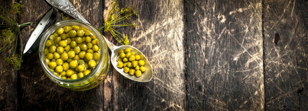 Pickled green peas in glass jar. On a wooden background.