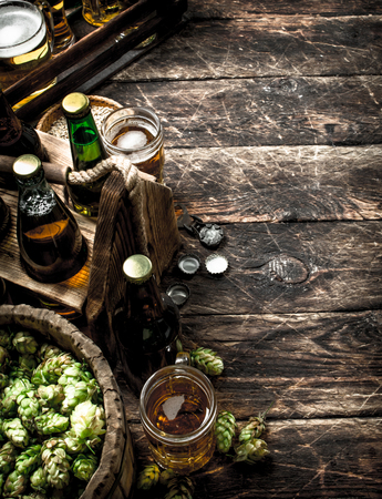 Fresh beer with green hops and malt. On a wooden background. Stok Fotoğraf