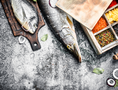 Fresh unprepared fish with spices. On a rustic background. Stock Photo