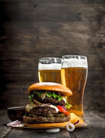길거리 음식. 라이트 맥주 잔을 가진 큰 햄버거. 목조 배경에.