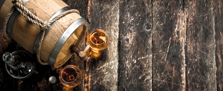 Old barrel with French cognac. On a wooden background.