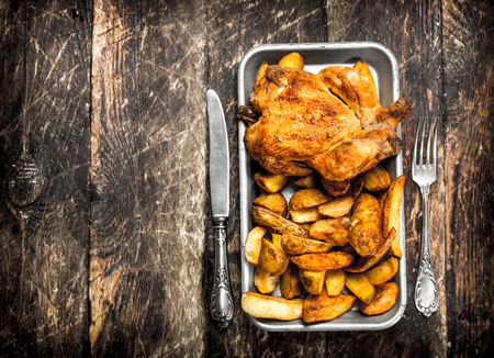 Fried potatoes with chicken on a tray. On a wooden background. Stock Photo
