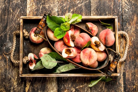 Ripe peaches on a tray. On a wooden background. Фото со стока