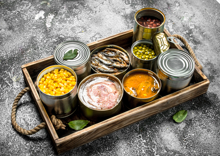 Various canned products in tin cans on a wooden tray. On a rustic background. Фото со стока - 92822879