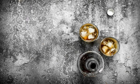 Whiskey with ice. On a rustic background.