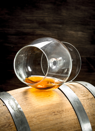 barrel with a glass of cognac. On a wooden background.