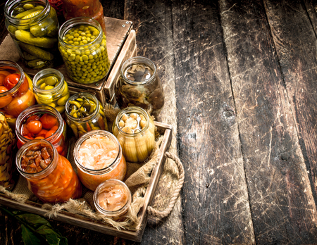 Preserves food with vegetables and mushrooms on an old tray. On a wooden background. Zdjęcie Seryjne