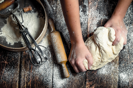 Dough background. Preparation of dough with tools. On a wooden table. 스톡 콘텐츠