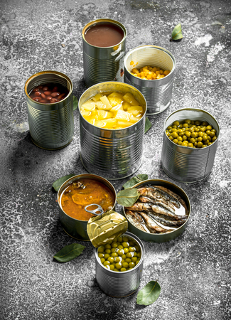 Various canned foods with meat, fish, vegetables and fruits in tin cans. On a rustic background. Foto de archivo