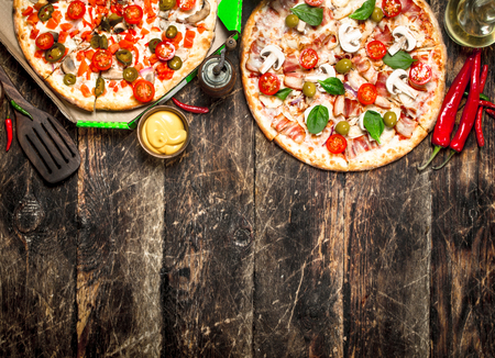 Two fresh pizzas with sauce. On a wooden background