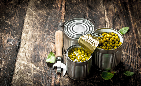Canned green peas in a tin can with opener. On a wooden background.