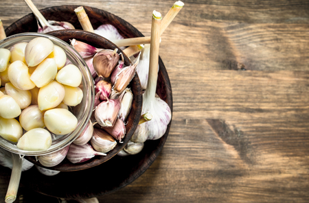 Fresh garlic in a wooden bowls. On a wooden table.