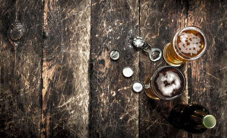 Fresh beer in a glass with stoppers and a bottle opener. On a wooden background.