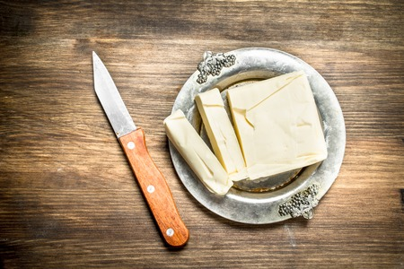 Butter with knife. On a wooden table.