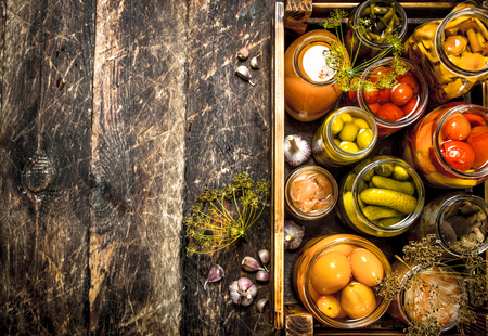Preserves mushrooms and vegetables in a box. On a wooden background. Stok Fotoğraf