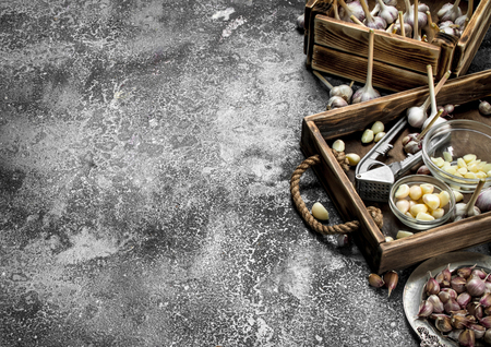 Fresh garlic with a press tool on a wooden tray. On a rustic background. Imagens