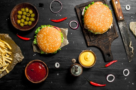 Street food. Fresh burgers with beef and vegetables. On the black chalkboard. 스톡 콘텐츠