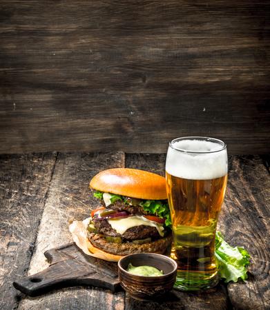 패스트 푸드. 쇠고기와 맥주 한 잔 함께 큰 햄버거. 목조 배경에.