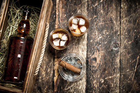 Whiskey background. A bottle of whiskey in an old box with glasses and a cigar. On a wooden background.
