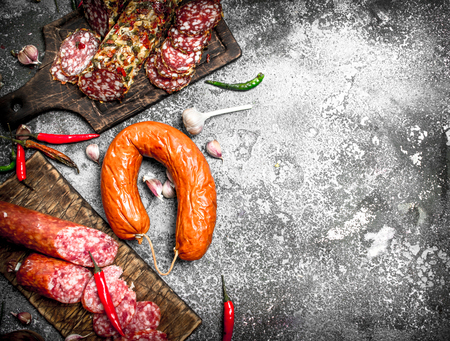 Salami background. Different kinds of salami with spices. On a rustic background.