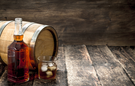 Whiskey background. A barrel of Scotch whiskey with glass and a cigar. On a wooden background. Stock Photo