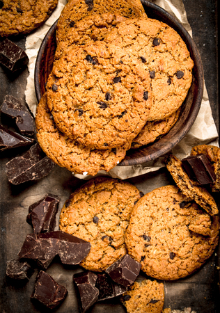 Oatmeal cookies with chocolate in a bowl. On a rustic background.