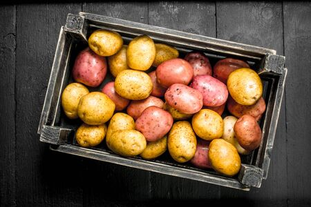 Fresh potatoes in an old box. On the black chalkboard. Stock Photo